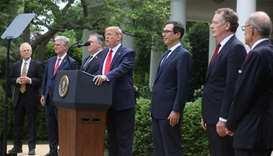 US President Donald Trump stands with members of his Cabinet as he makes an announcement about US tr