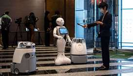"A reporter (R) records the greeting voice of a robot called ""Pepper"" (C) with two other cleaning rob"