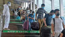 Passengers queue as they are checked by health workers upon their arrival from New Delhi at New Jalp