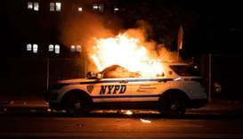 A NYPD police car is set on fire as protesters clash with police during a march against the death in