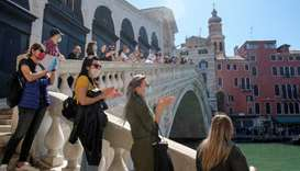 A rally organised by small business owners stops by the Rialto bridge to commemorate the health care