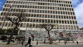 A woman wearing a protective mask walks past Central Bank building as Lebanon extends a shutdown to