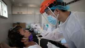 A nurse gets a swab from a man under observation for coronavirus disease (COVID-19) in a booth set u