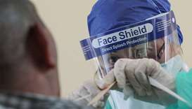 A health worker, wearing personal protective equipment, collects a swab sample from a man at a drive