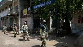 Border Security Force (BSF) soldiers patrol along a street during a government-imposed nationwide lo