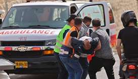 Palestinian medics evacuate a wounded protester amid clashes with Israeli security forces in Jerusal