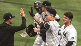 New York Yankees' Giancarlo Stanton (centre) celebrates with teammates and coaches after hitting a w