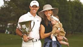 Rory McIlroy of Northern Ireland celebrates with the trophy alongside his wife Erica and daughter Po