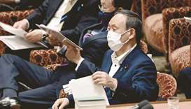 Japan's Prime Minister Yoshihide Suga (R) attends a lower house budget committee session in Tokyo ye