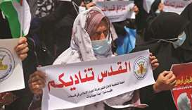 "An elderly Palestinian woman stands with a sign reading in Arabic ""Jerusalem calls upon you"" during"