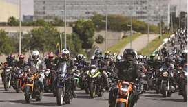 Bolsonaro gestures as he and his supporters ride motorcycles to celebrate the National Mother's Day