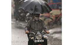 A commuter makes his way along a street during a rainfall in Amritsar yesterday. India's top oil ref