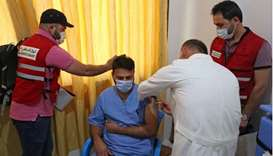 A medical worker receives a dose of the AstraZeneca Covid-19 vaccine in the presence of Qatar Red Cr