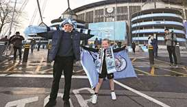 Young Manchester City fans celebrate their club winning the Premier League title, outside the Et