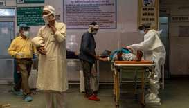 A man speaks on the phone as a doctor tries to revive his wife inside an emergency ward of a governm