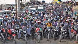 People on motorcycles rush to board a ferry at Mawa Ferry Terminal in Munshiganj, Bangladesh, to get