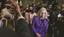 An aide motions for US Representative Liz Cheney to exit after taking a final question from reporter