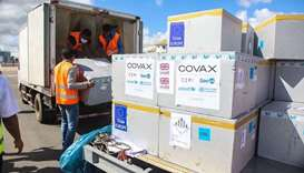 Workers load boxes of Oxford/AstraZeneca Covid-19 vaccines, part of the the Covax programme, which a