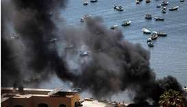 Plumes of black smoke rise during an Israeli air strike at the seaport of Gaza City