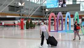 People wearing masks walk through a mostly empty domestic terminal at Sydney Airport in Sydney, Aust