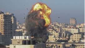 A fireball and smoke billow up into the air during an Israeli airstrike on Gaza City targeting the A
