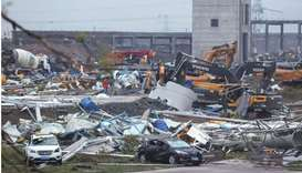 Damaged vehicles and debris are pictured at a construction site after a tornado hit an economic zone