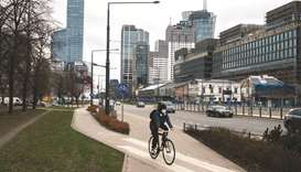 A cyclist uses a cycle lane near offices and skyscrapers in the financial district in Warsaw. The Po