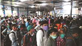 People queue up to buy tickets to return home at a bus station in Kolkata after the West Bengal gove