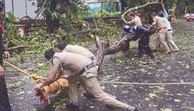 Police personnel clear fallen trees from a road following strong winds caused by the impending cyclo