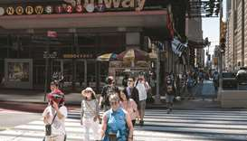 People walk past a subway stop sign as the subway returns to 24-hour service, in New York City, yest