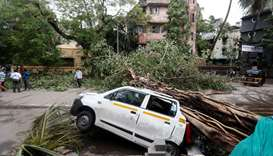 An uprooted tree is seen fallen on a car after strong winds caused by Cyclone Tauktae, in Mumbai, In