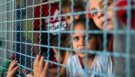 Palestinian children, who fled their homes due to Israeli air and artillery strikes, look through a