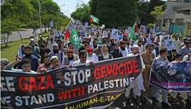 Demonstrators hold placards and shout slogans as they march in support of Palestine during an anti-I