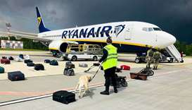 A Belarusian dog handler checks luggages off a Ryanair Boeing 737-8AS (flight number FR4978) parked
