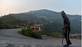 An elderly man walks along a deserted hill road during a partial lockdown imposed as preventive meas