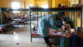 A doctor checks the medicines of a patient suffering from coronavirus disease inside a classroom tur