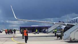 Airport personnel and security forces are seen on the tarmac in front of a Ryanair flight which was