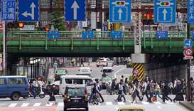 Commuters walk near Shinjuku Station in Tokyo after the announcement that the governemrnt extended a