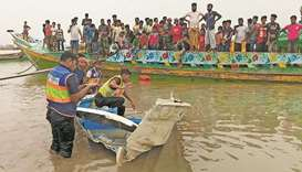 Policemen inspect the speedboat that was carrying passengers when it collided with a vessel transpor