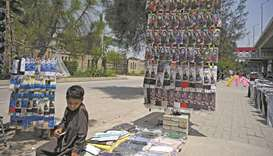 A boy selling face masks waits for customers at a stall along a street in Rawalpindi.