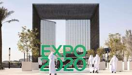 A man photographs the official sign marking the Dubai Expo 2020 near the Sustainability Pavilion in