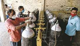 Employees at an oxygen refilling centre in Moradabad, India, refill cylinders for coronavirus patien
