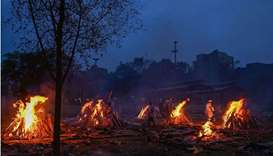 Volunteers help the burning of funeral pyres of people who died due to the Covid-19 coronavirus, at