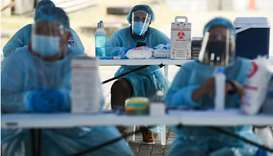 Health workers wait for the arrival of residents to be vaccinated against the coronavirus disease (C