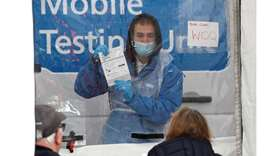 An NHS worker explains the coronavirus disease testing protocol to local residents at a mobile testi