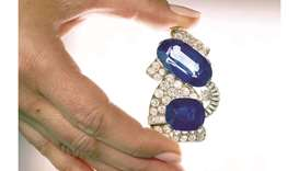A staff holds a 1930s sapphire and diamond brooch, featuring the largest Kashmir sapphire ever to ap