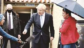 Britain's Prime Minister Boris Johnson jokes with a journalist (left) as he is greeted by a supporte
