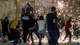 Palestinians react as Israeli police fire stun grenades during clashes at the compound that houses A