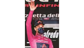 Team Ineos rider Italy's Filippo Ganna, wearing the overall leader's pink jersey, waves on the podiu