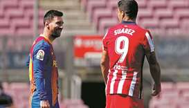 Atletico Madrid's Luis Suarez (right) speaks with Barcelona's Lionel Messi before the La Liga match